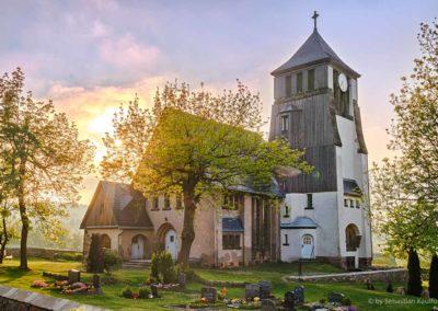 Die Kirche Zinnwald im sommerlichen Sonnenuntergang.